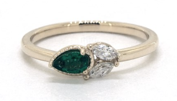 Yellow gold engagement ring with emerald and diamond cluster